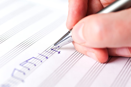 Hand writing music notes close-up