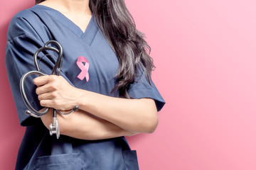 Woman doctor holding a stethoscope on her hands with pink ribbon over pink background