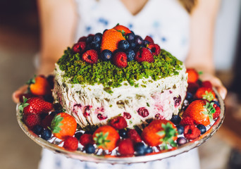 Woman presenting a birthday cake with fresh fruits. Healthy dessert