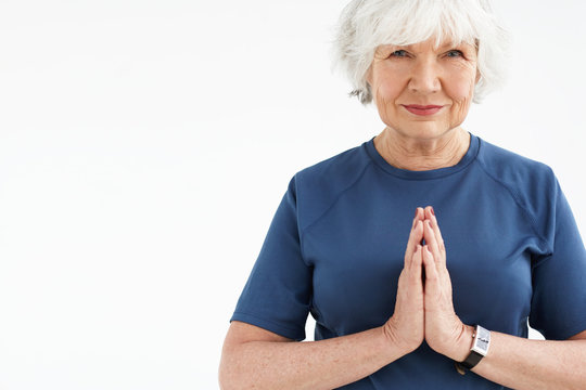 Positive energetic elderly woman with gray hair choosing active healthy lifestyle, smling, holding hands in namaste while practicing yoga or meditation against blank copyspace studio wall background