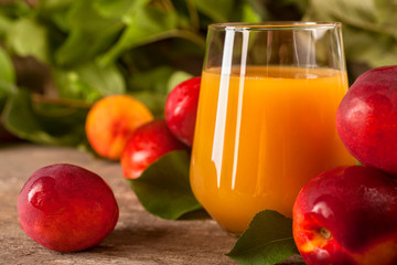 Glass of nectarine juice with fresh nectarines on rustic background