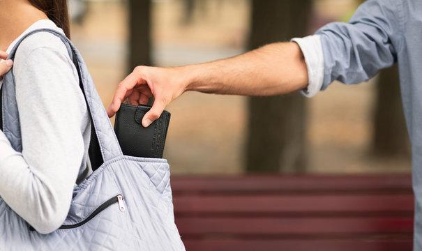 Pickpocket thief stealing wallet from woman handbag