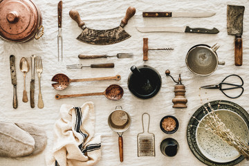 Flat-lay of various kitchen utensils, rustic tablewear, plates, dishes, glasswear, pan, scissors, corkscrew, textile for cooking over white linen tablecloth background, top view. Seasonal cooking