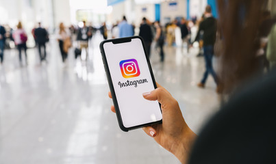BERLIN, GERMANY AUGUST 2019: Woman hand holding iphone Xs with logo of instagram application at a conference. Instagram is largest and most popular photograph social networking.