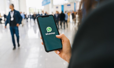 WhatsApp Business BERLIN, GERMANY AUGUST 2019:   Woman holding a iPhone Xs opening Whatsapp app on a conference. WhatsApp messenger for sending messages via the Internet.