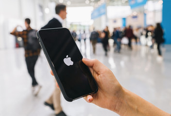 BERLIN, GERMANY AUGUST 2019:   Woman hand holding iphone Xs with logo of apple, produced by Apple Computer, Inc.