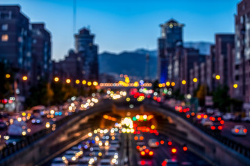 Blurred and Famous view of Tehran,Flow of traffic around Tohid Tunnel with Milad Tower and Alborz Mountains in Background, night cityscape concept