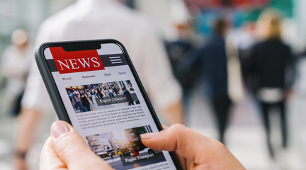 Online news on a mobile phone. Close up of businesswoman reading news or articles in a smartphone...