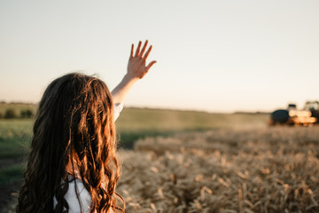 Young woman standing back on field and waving hand to a tractor driver in sunset. Fotoväggar