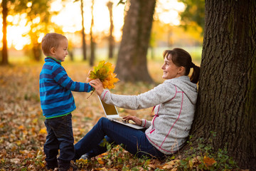 Child giving bunch of autumn leaves to his mother