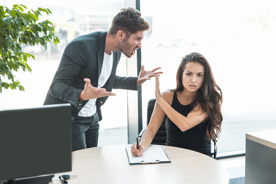 strict boss man swearing at employee woman for bad work at the office