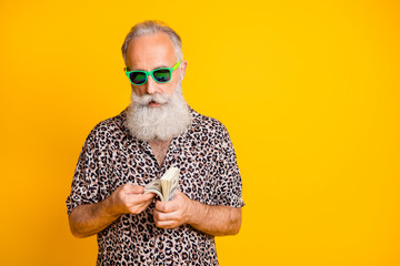Portrait of modern funky funny old bearded man in stylish eyewear eyeglasses true worker on resort count money credit deposit wear leopard shirt isolated over yellow background