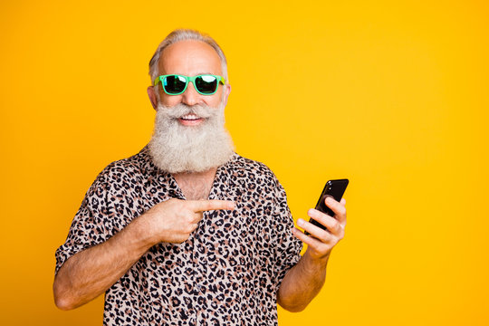Portrait of funny funky old bearded hipster use point his cellphone find online sales discounts apps on summer holidays wear leopard shirt isolated over yellow background