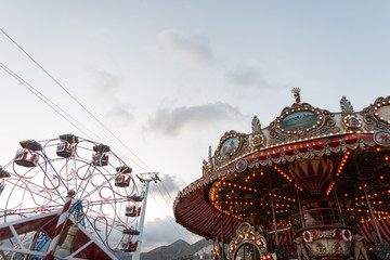 View on vintage beautiful carousel with bright lights with orange bulbs and on a ferris wheel. Amusement park on the background sky on a summer day. Wall mural