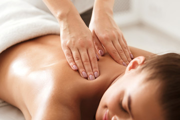 Young woman enjoying therapeutic neck massage in spa