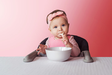 Nine-month-old baby girl in pink bandage sits at white table in highchair, eats herself with spoon from bowl. Pink background.