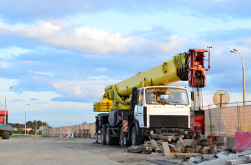 Unloading of cargo and building materials by mobile truck crane at the construction site. Auto crane during the construction of a bridge and highway road - Image
