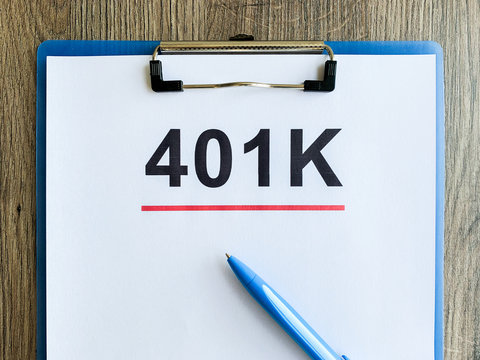 Paper with 401k plan on wood table.