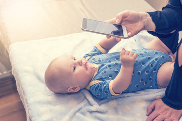 Photographed infant is lying on the table. Woman is taking picture by smart phone. Baby is stretching hands on the phone. All potential trademarks are removed.