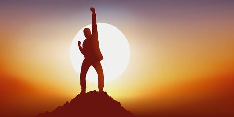 Concept du leadership avec un homme qui exprime sa joie en levant le point en signe de victoire en atteignant le premier le sommet d'une montagne