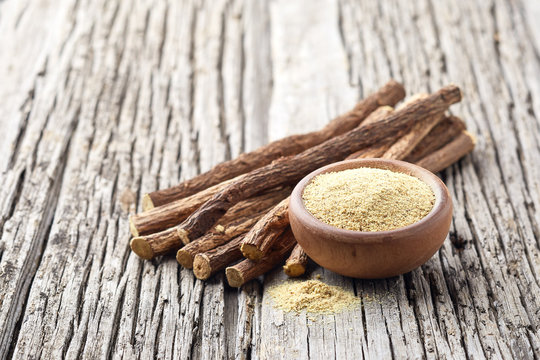 Licorice dry root with powder on wooden background