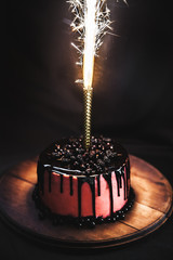 Cake with berries on a black background. Festive candle with fireworks. Birthday