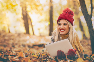 Beautiful young woman lying in autumn city park and using digital tablet scrolling touch screen