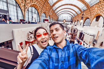 27 July 2019, Paris, France: Boy and Girl tourists visiting the famous Orsay Museum with sculptures and impressionist paintings and taking selfie photo together