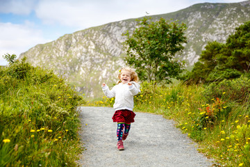 Cute little happy toddler girl running on nature path in Glenveagh national park in Ireland. Smiling and laughing baby child having fun spending family vacations in nature. Traveling with small kids