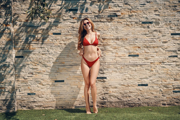 Full length of attractive young woman in bikini smiling while standing outdoors