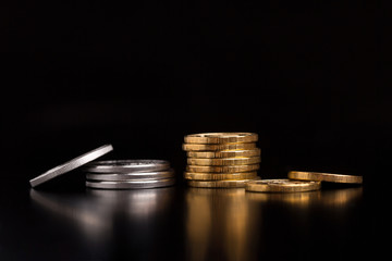 A stack of silver and gold coins. Silver and gold coins on a black background.Coins side view close up.