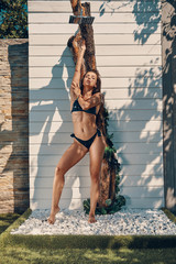 Full length of attractive young woman in bikini relaxing while taking refreshing shower outdoors