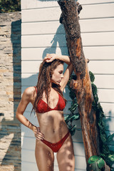 Attractive young woman in bikini relaxing while taking refreshing shower outdoors