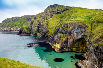 View from Carrick-a-Rede Rope Bridge, famous rope bridge near Ballintoy in County Antrim, Northern Ireland on Irish coastline. Tourist attraction, bridge to small island on cloudy day.