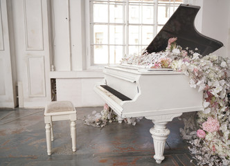 white grand piano with spring white and pink flowers in a white room with nobody