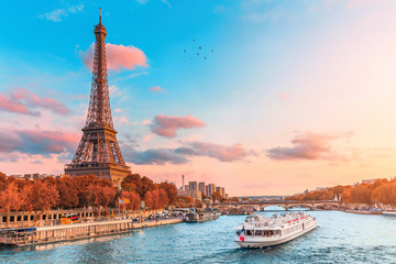 Poster de jardin Tour Eiffel The main attraction of Paris and all of Europe is the Eiffel tower in the rays of the setting sun on the bank of Seine river with cruise tourist ships