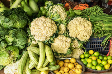 Some vegetables, like as cauliflower, cabbage, kale, carrots, zucchini, limes in a farmers market.