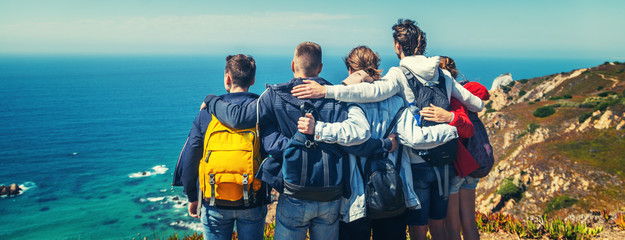 A company of young happy friends travels in Portugal, stands on the shore of the Atlantic Ocean and hugs, travell together, community friendship vacation