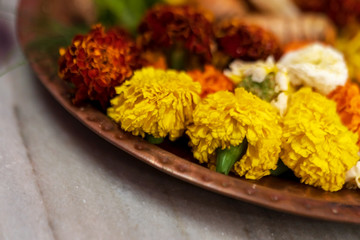 Horizontal Shot Of Durga Puja Thali. Closeup horizontal side angle shot of marigold flowers on a thali or plate for puja preparations. Background picture of Hindu traditional rituals with copy space.