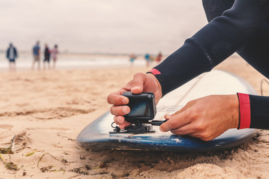 Male surfer attaches an action camera to a surfboard, sport and entertainment concept