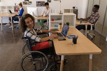 Disabled female executive using laptop at desk