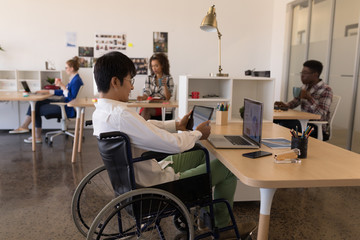 Disabled male executive using digital tablet at desk