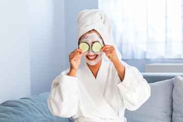 Woman with facial mask and cucumber slices in her hands. Beautiful young woman with facial mask on her face holding slices of fresh cucumber. Young woman with clay facial mask holding cucumber slices