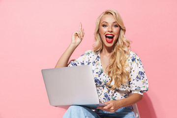 Image of excited woman using silver laptop while sitting on chair