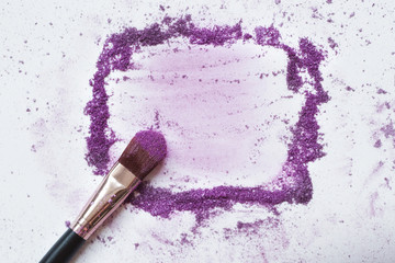 A makeup brush on a white background, with traces of  eye shadow on it forming a frame. A horizontal template for a makeup school business card or flyer design, with plenty of copyspace