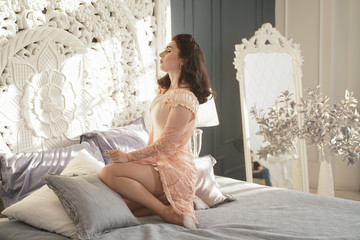 a gentle slender young girl in a pink strongly tightening corset and beige classic nylon stockings in her bedroom