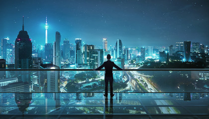 Photo Stands Kuala Lumpur Businessman standing at transparent glass floor on rooftop with night city panoramic view.