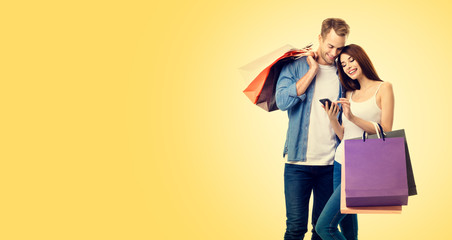 Picture of happy smiling lovely couple with smartphone and shopping bags, against yellow color background