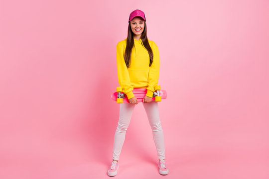 Full length body size photo of cheerful charming cute beautiful sporty girlfriend ready to skateboard wearing yellow sweater isolated over pink pastel color background