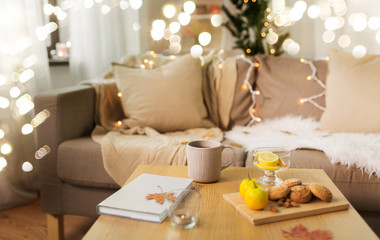 Fototapete - hygge and cozy home concept - cup of tea with lemon, book, autumn leaves and oatmeal cookies on wooden table in living room
